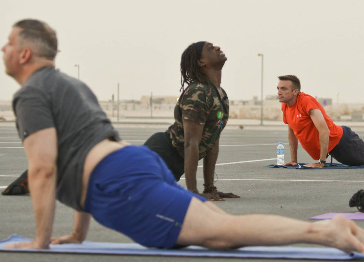 Men doing power yoga outside